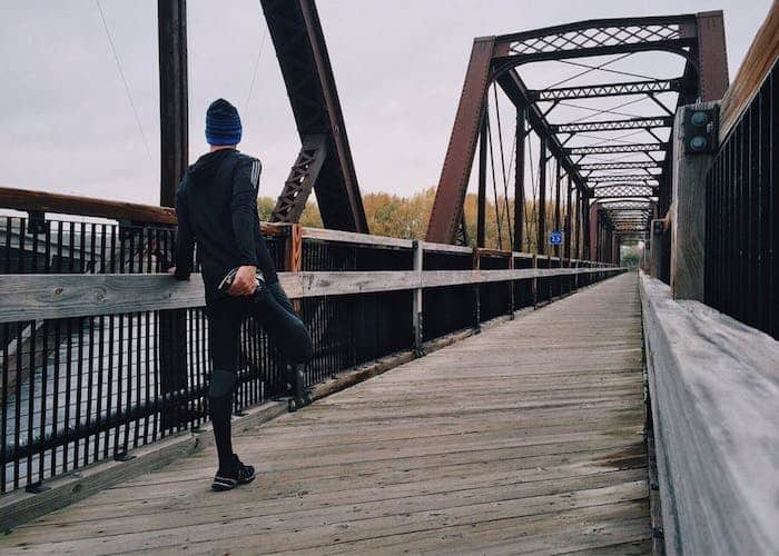 Guy on bridge stretching before run